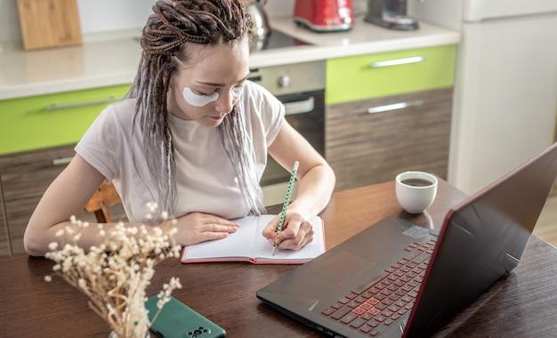 Mulher moderna com máscara cosmética no rosto e trabalhando em casa usando um laptop