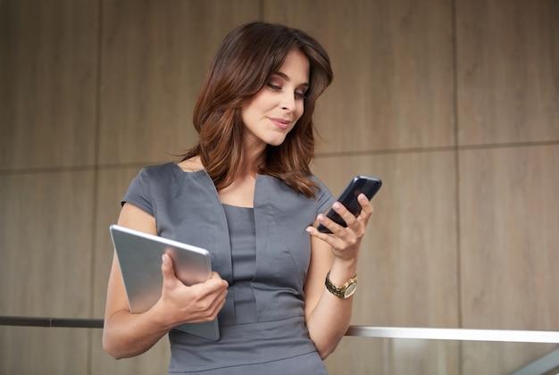 Mulher moderna com telefone e tablet digital