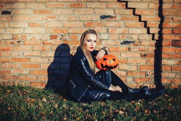Mulher moderna de halloween. bruxa atraente segurando abóbora 'gostosuras ou travessuras'. mulher vestindo jaqueta de couro e saia preta. outubro dia das bruxas. fundo de tijolos
