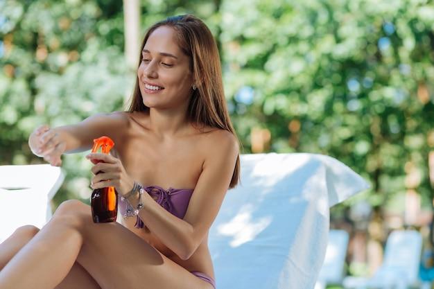 Mulher moderna e saudável cuidando da pele antes de se bronzear enquanto está sentada perto da piscina