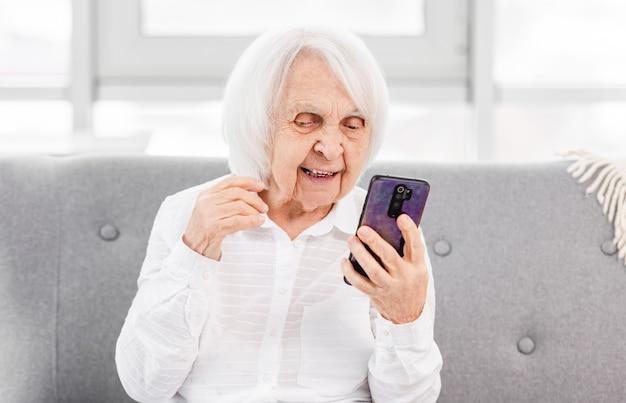 Mulher moderna ederly falando com amigos por vídeo usando o smartphone. conceito de velha geração e novas tecnologias