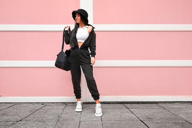 Mulher moderna elegante e esportiva usando macacão preto, chapéu-panamá, blusa branca curta e botas