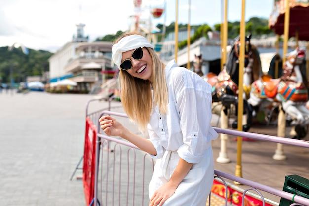 Mulher moderna elegante e feliz vestida de shorts e camisa branca, óculos de sol pretos se divertindo do lado de fora no parque de atrações em um dia ensolarado, emoções felizes, conceito de estilo de vida, semana de verão e