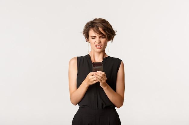 Mulher moderna elegante parecendo enojada com a tela do telefone móvel, encolhida de algo horrível, branco de pé