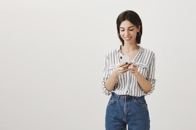 Mulher moderna elegante usando telefone celular, olhando para o smartphone com um sorriso satisfeito