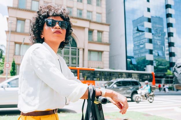 Mulher moderna em uma cidade com uma scooter elétrica