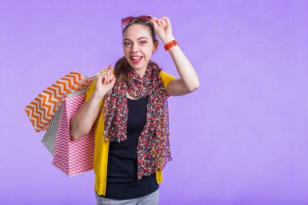 Mulher moderna feliz segurando o saco de papel decorativo na frente da parede roxa