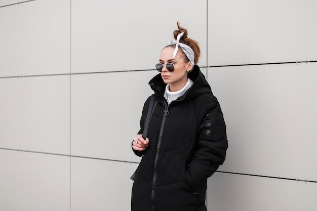Mulher moderna jovem hippie em óculos de sol redondos com um casaco elegante em uma bandana da moda com uma mochila de couro está de pé perto de uma parede branca num dia quente de inverno. garota americana elegante de férias