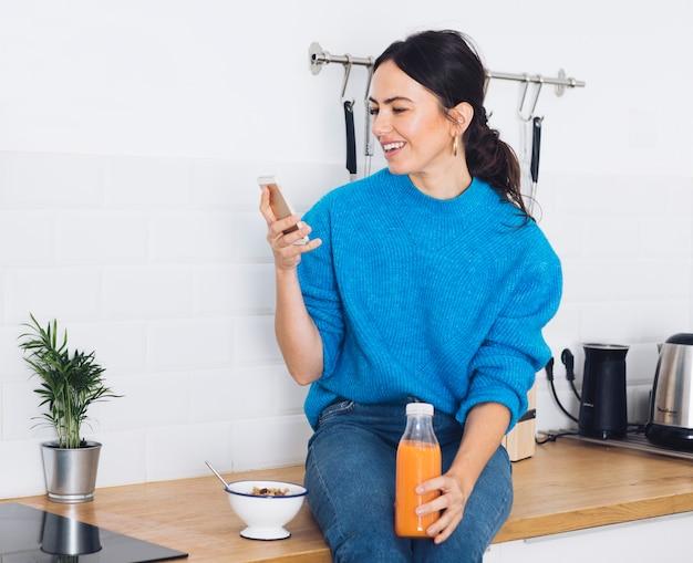 Mulher moderna tomando café da manhã na cozinha