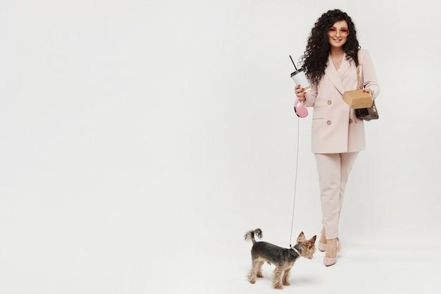 Mulher modish com uma xícara de café plástica e um cão pequeno bonito que anda no fundo branco, isolado. maquete do conceito de moda urbana.
