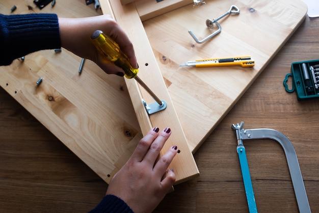 Mulher montando móveis de madeira consertando ou consertando casa com chave de fenda