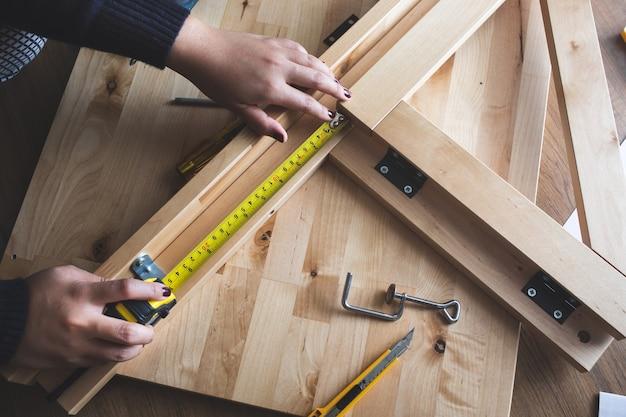 Mulher montando móveis de madeira consertando ou consertando casa com fitas métricas