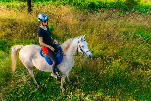 Mulher, montando um cavalo branco na vista superior