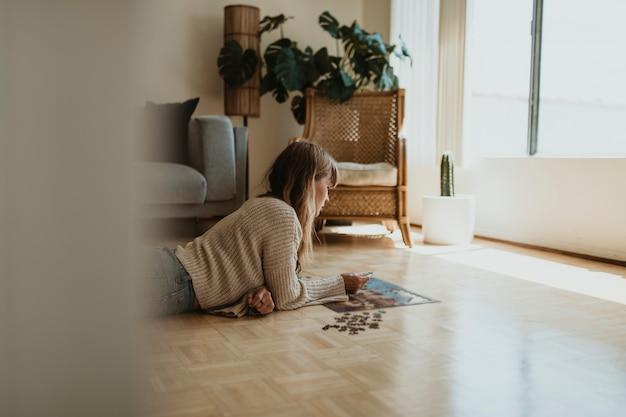 Mulher montando um quebra-cabeça durante a auto-quarentena