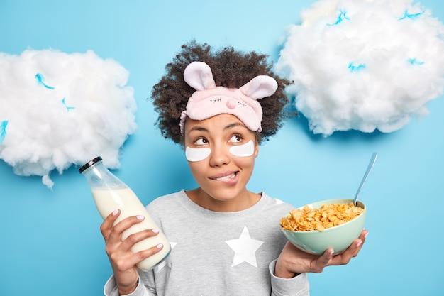 Mulher morde lábios indo tomar café da manhã segura tigela de cereais e garrafa de leite usa pijama aplica manchas embaixo dos olhos para remover rugas isoladas no azul