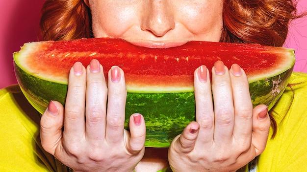 Mulher mordendo uma fatia de melancia