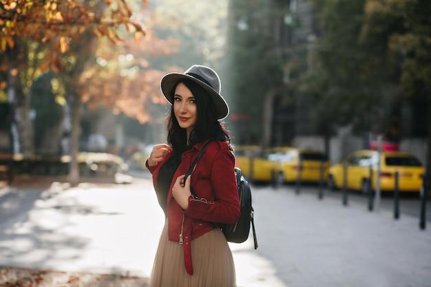 Mulher morena adorável com mochila passando um tempo ao ar livre em um dia ensolarado
