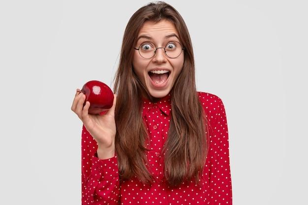 Mulher morena alegre abre a boca amplamente, tem uma expressão feliz, usa óculos redondos, camisa de bolinhas vermelhas, segura maçã fresca