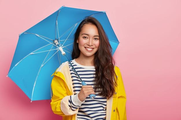 Mulher morena alegre asain com longos cabelos escuros, usa um macacão listrado, capa de chuva amarela, segura guarda-chuva azul, faz um passeio em dia chuvoso