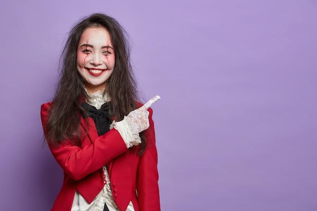 Mulher morena alegre assustadora com cicatrizes e rosto pálido indica no espaço vazio, vestida com fantasia de carnaval, mostra a direção contra a parede roxa. tema de terror