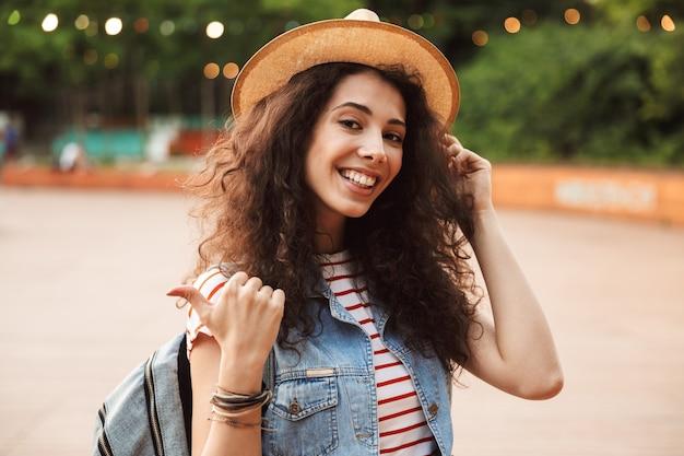 Mulher morena alegre com cabelo castanho encaracolado, sorrindo e apontando o dedo de lado enquanto caminha em um lugar moderno ou parque moderno