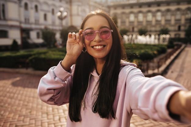 Mulher morena alegre com capuz rosa e óculos de sol da moda sorri sinceramente e tira uma selfie de bom humor lá fora