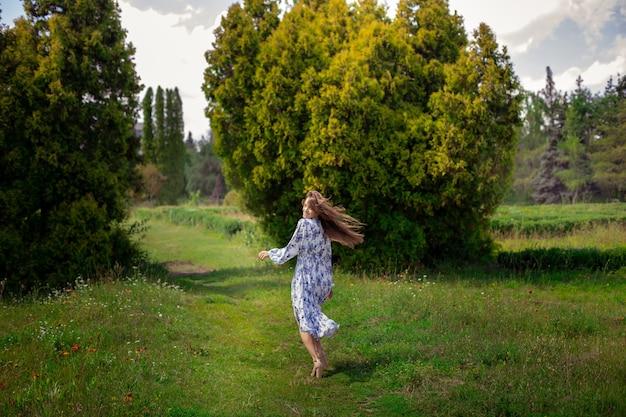Mulher morena alegre de salto alto andando em um vestido longo com estampa de flores no parque