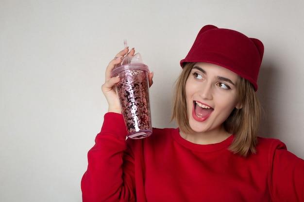 Mulher morena alegre de suéter vermelho e boné segurando o copo de suco de cereja. espaço para texto