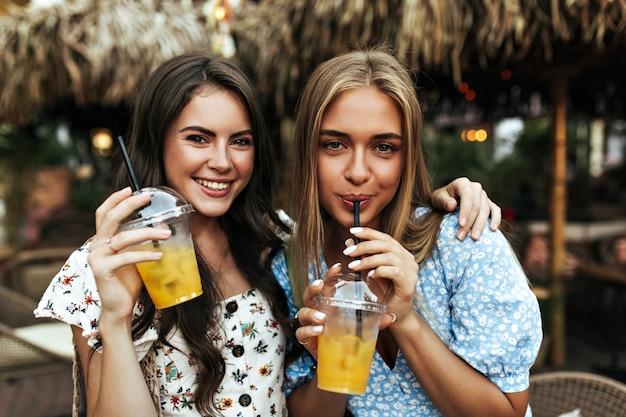 Mulher morena alegre e encaracolada em uma blusa da moda floral e uma garota loira bronzeada com top azul sorriem e segurando copos de limonada do lado de fora