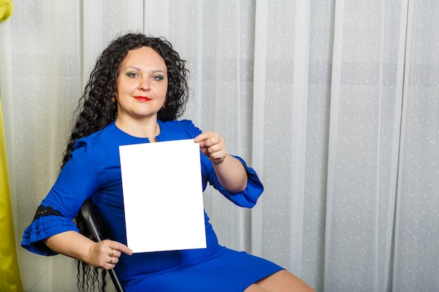 Mulher morena alegre e encaracolada em uma cadeira tem uma placa de espaço de cópia nas mãos. foto horizontal