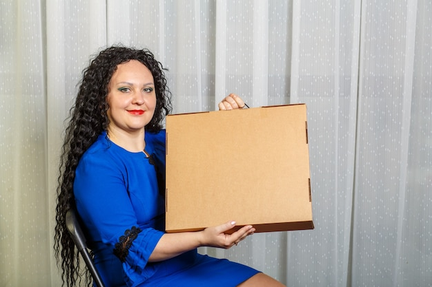 Mulher morena alegre e encaracolada tem nas mãos uma compra tão esperada mostra a ela. foto horizontal