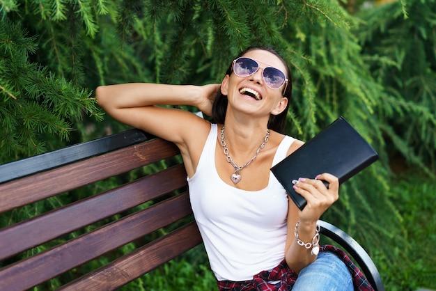 Mulher morena alegre em roupas casuais e óculos escuros se senta em um banco de madeira no parque contra ...