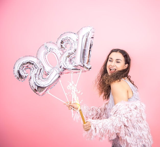 Mulher morena alegre festa com cabelo encaracolado vestida festivamente segurando uma vela de fogos de artifício na mão e balões de prata para o conceito de ano novo