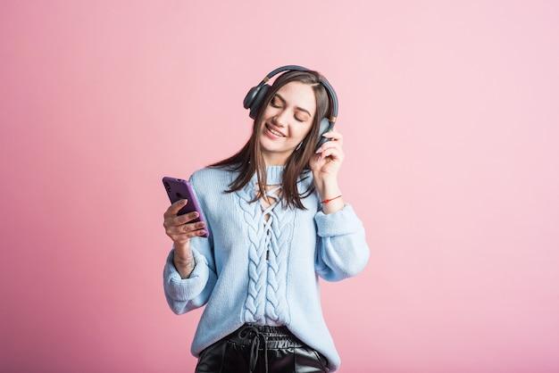 Mulher morena alegre ouve música em fones de ouvido com um smartphone