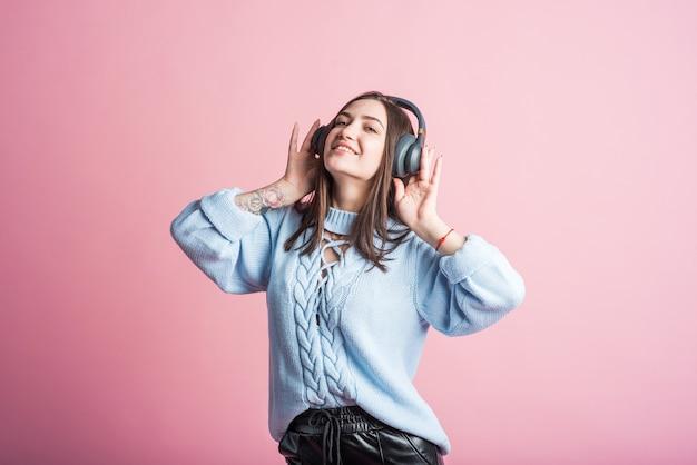 Mulher morena alegre ouve música em fones de ouvido no estúdio em um fundo rosa