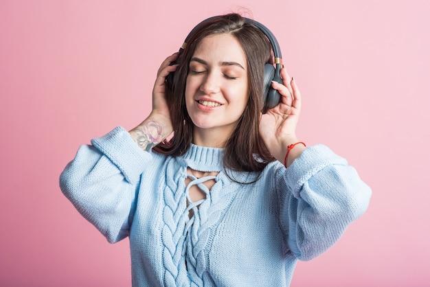 Mulher morena alegre ouvindo música em fones de ouvido