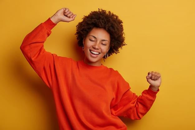 Mulher morena alegre se diverte e dança com as mãos levantadas, vestida com blusão casual, aplausos sobre fundo amarelo, obtém promoção ou aprovação, comemora a vitória.