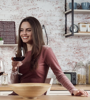 Mulher morena alegre segurando uma taça de vinho tinto