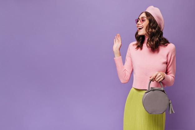 Mulher morena animada com saia verde, boina rosa e suéter acenando para cumprimentar