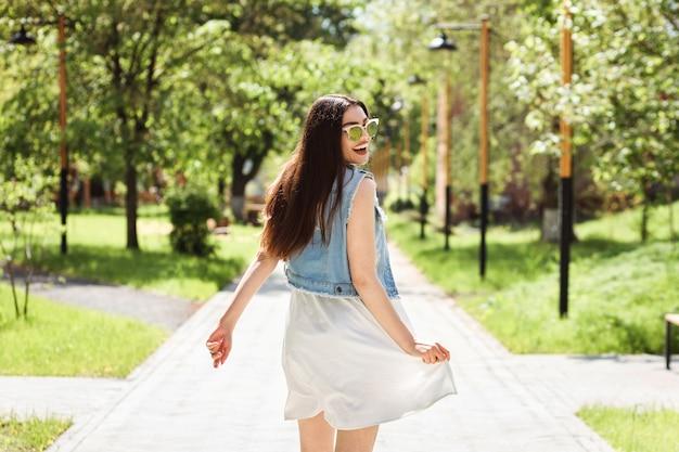 Mulher morena atraente alegre está se divertindo ao ar livre no parque no verão.