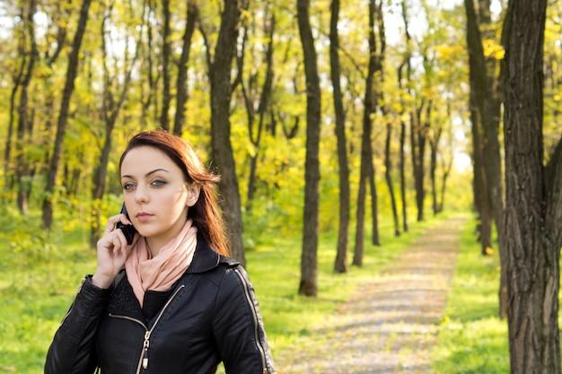 Mulher morena atraente caminhando por uma trilha pavimentada em um parque, falando ao celular