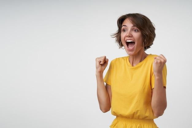 Mulher morena atraente com cabelo castanho curto e selvagem de alegria enquanto torce pelo seu time favorito, levantando os punhos e gritando feliz, posando