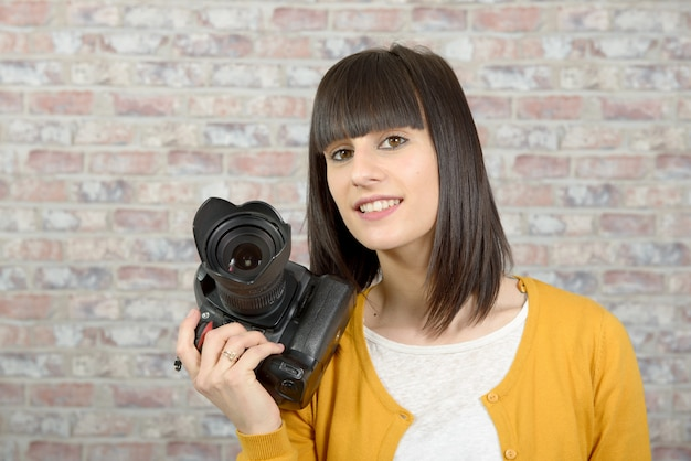 Mulher morena atraente com câmera fotográfica