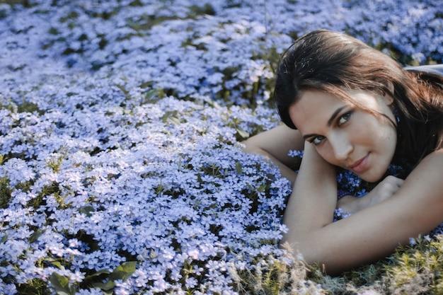 Mulher morena atraente com olhar sexy está deitado no quintal com flores azuis