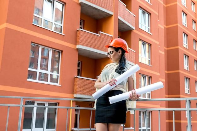Mulher morena atraente com projetos no capacete de construtor
