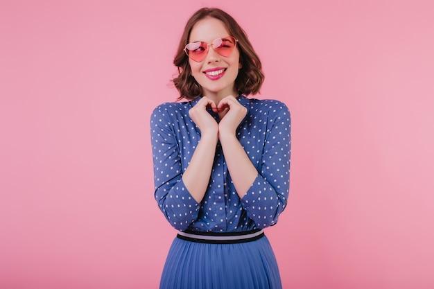 Mulher morena atraente com saia longa azul brincando brincando na parede pastel. rindo garota deslumbrante na blusa elegante, expressando emoções positivas.