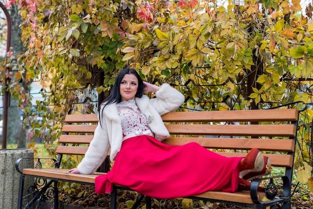 Mulher morena atraente com vestido vermelho sentada em um banco no parque outono