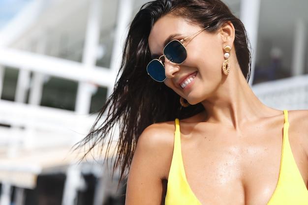 Mulher morena atraente de biquíni e óculos escuros, rindo e sorrindo, relaxando na piscina do spa em um dia ensolarado.