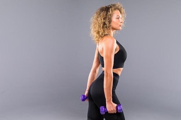 Mulher morena atraente e desportiva em sportswear preto detém halteres isolados na parede cinza.