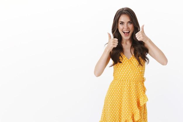 Mulher morena atraente e otimista torcendo por uma escolha excelente, mostrar sinal de aprovação com os polegares, sorrindo satisfeito, concordar com a ideia incrível, regozijando, julgando roupa, parede branca